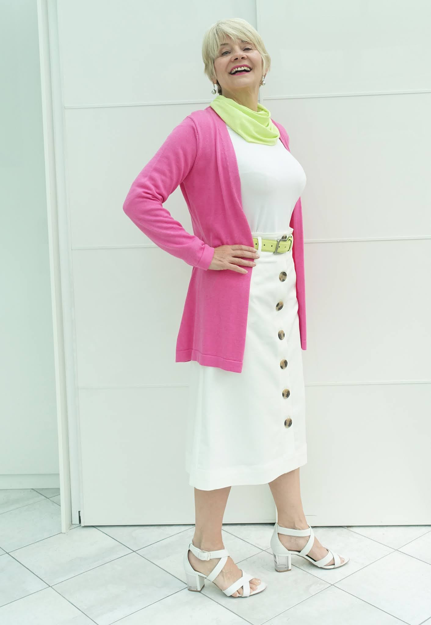 All-white outfit with punchy accents of cerise pink and acid yellow worn by over-60 blogger Gail Hanlon from Is This Mutton