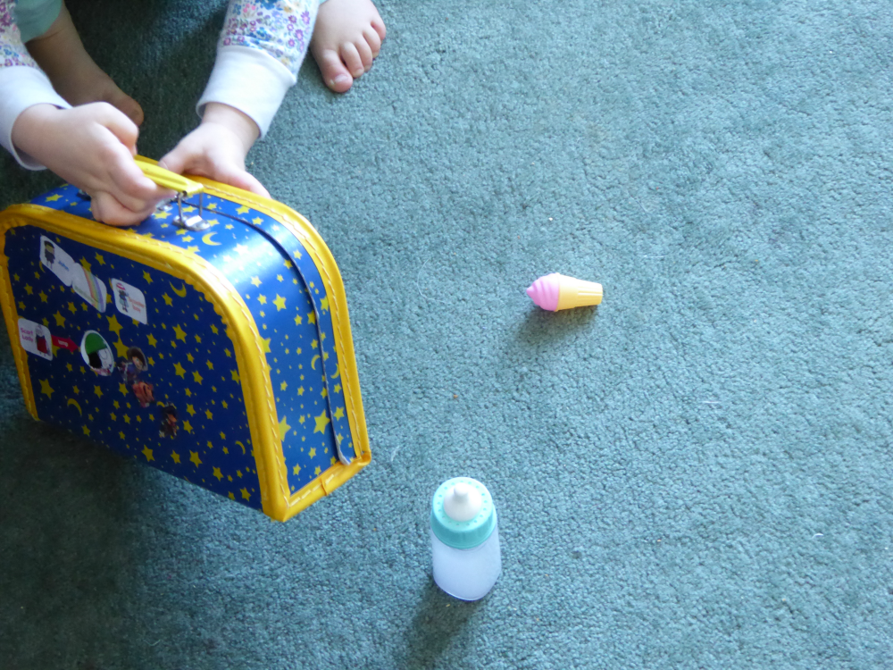 Toddler hands holding suitcase