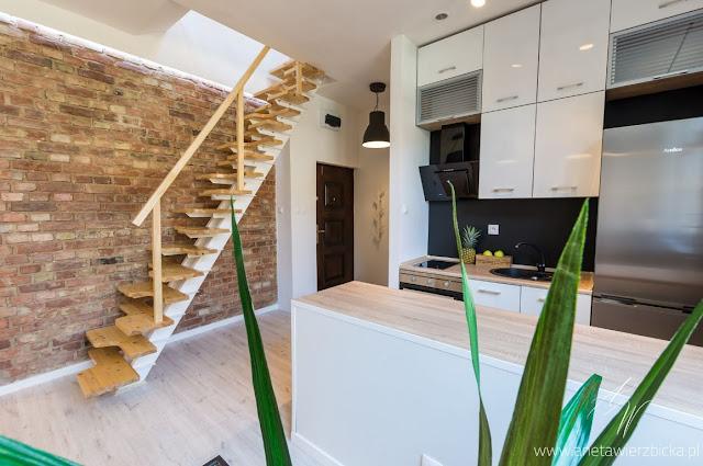 Idealne wnętrze, to wnętrze nieprzekombinowane. Aranżacja kuchni z wyspą i wejście na piętro z prostymi, drewnianymi schodami.