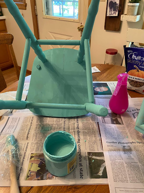 Photo of a child's chair being painted turquoise