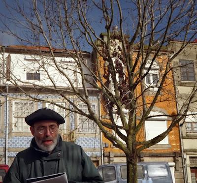 senhor lendo em frente à edifícios do Porto