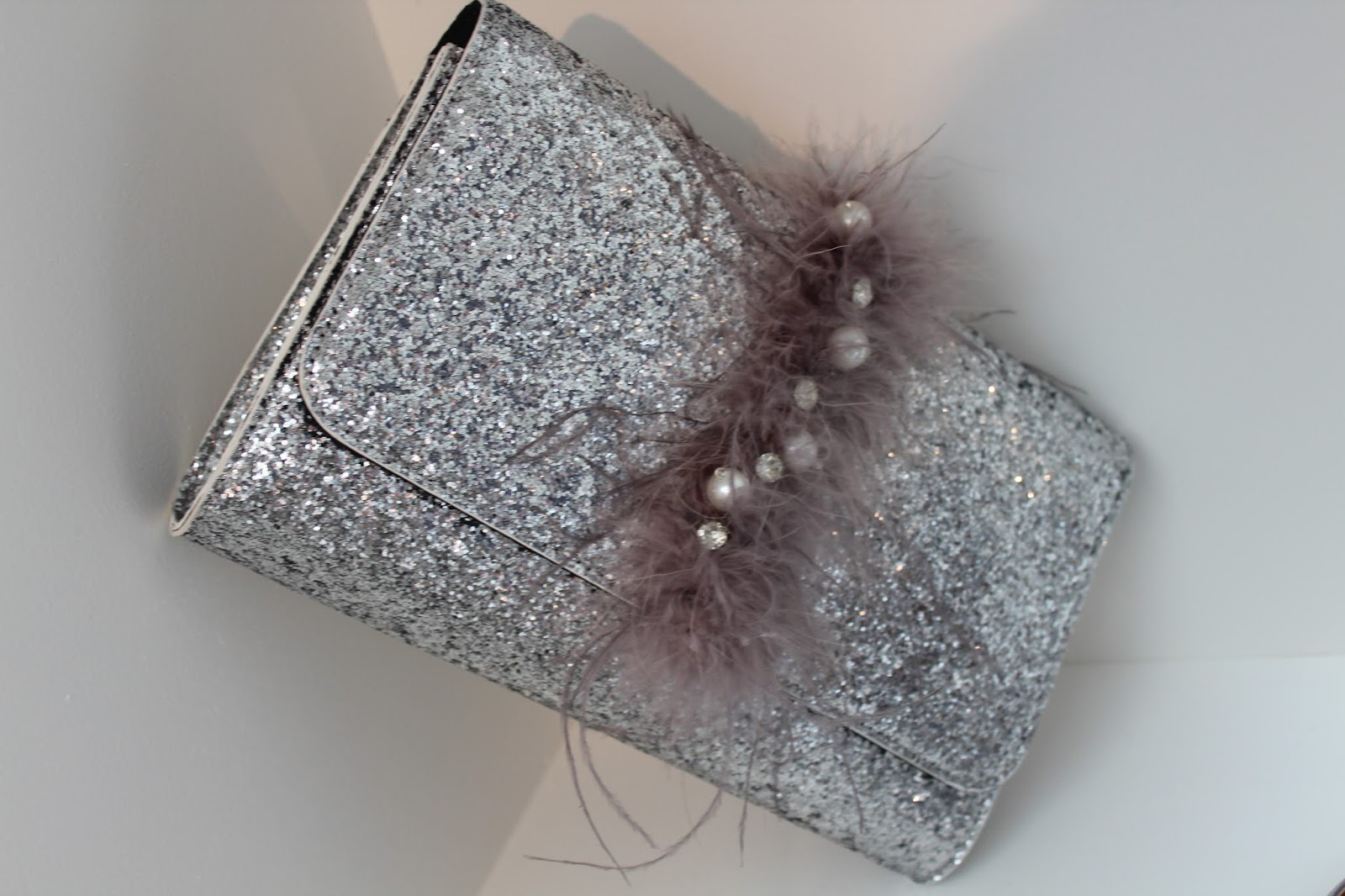 ef36495b247 *In Store* This lovely V by Very clutch has got all the new trends for the  perfect party bag. It is glittering with a central stripe made of feathers,  ...