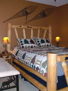 Bedroom with a log bed, down comforter, brown walls, snowshoes hanging on the wall, with beige carpet.  Moose theme bedside lamps and tables.