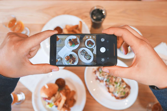 A picture of two hands holding an iPhone, taking a picture of food