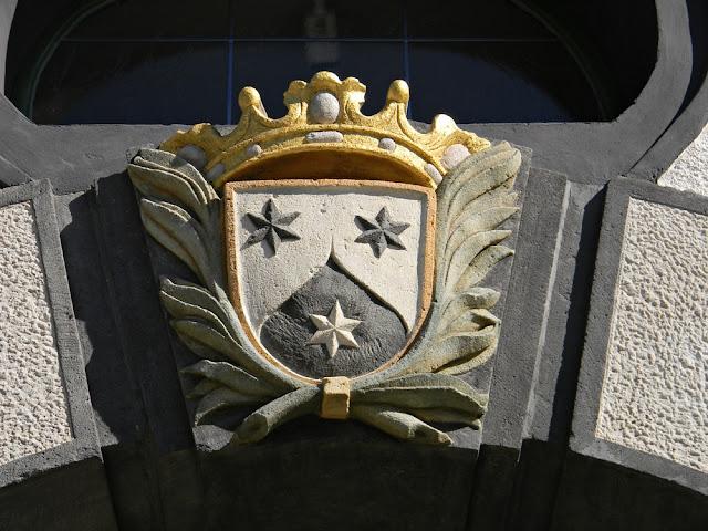 Herb przedstawia trzy gwiazdy, dwie u góry i jedną na dole.