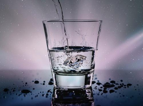 Líquido enchendo copo que está pela metade, gotas ao redor. #PraCegoVer
