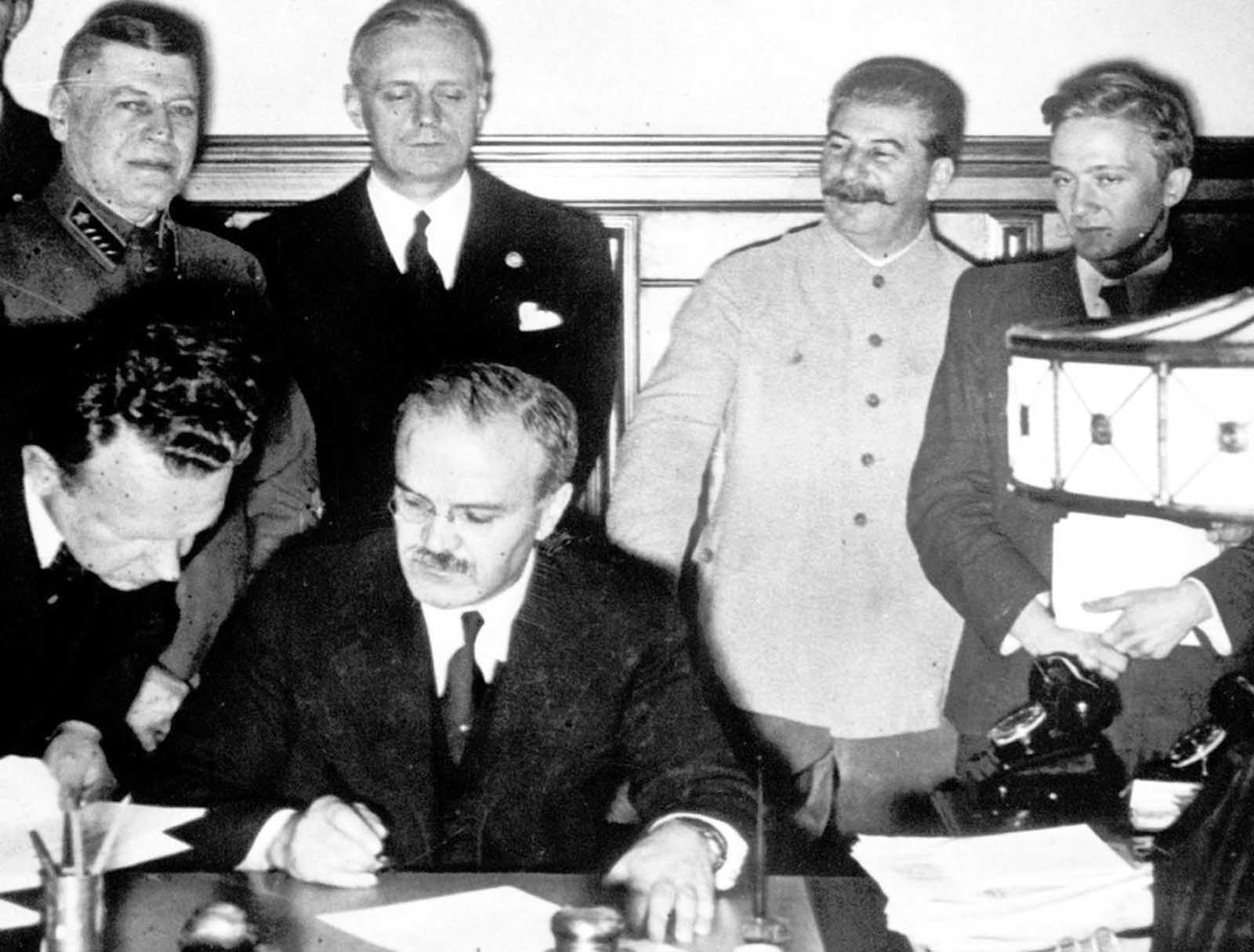 Soviet premier Josef Stalin (second from right), smiles while Soviet Foreign Minister Vyacheslav Molotov (seated), signs the non-aggression pact with German Reich Foreign Minister Joachim von Ribbentrop (third from right), in Moscow, on August 23, 1939. The man at left is Soviet Deputy Defense Minister and Chief of the General Staff, Marshal Boris Shaposhnikov. The nonaggression pact included a secret protocol dividing eastern Europe into spheres of influence in the event of a conflict. The pact now guaranteed that Hitler's troops would face no resistance from the Soviets if they invaded Poland, bringing the war one step closer to reality.