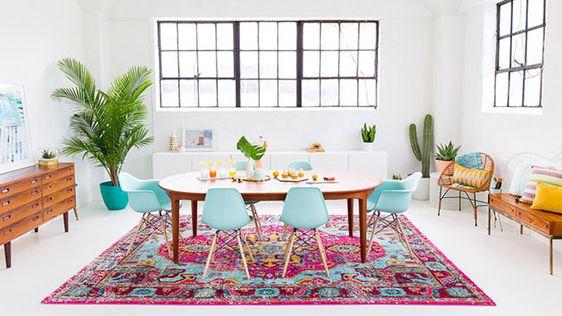 estilo decoración salón blanco con mesa de madera y sillas de colores