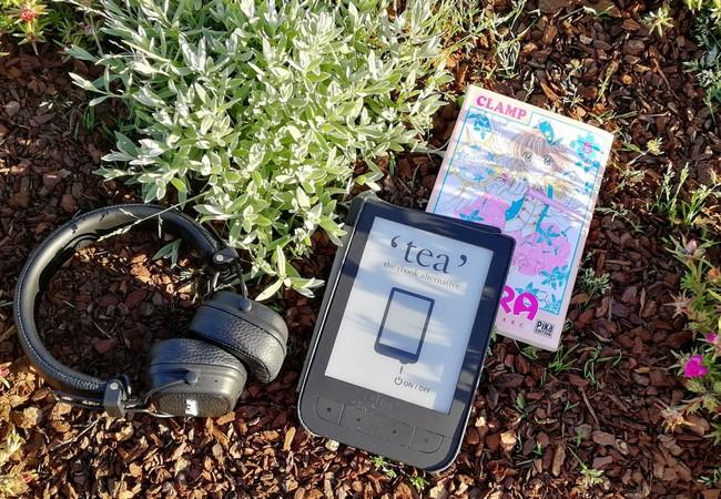 Casque audio, liseuse et manga posés dans les plantes de ma terrasse.