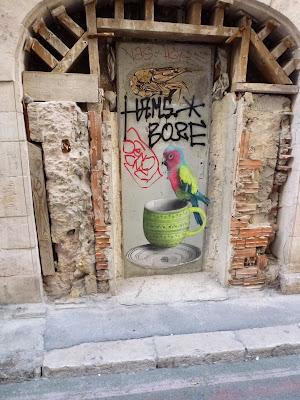 """Gesamtansicht: bunter Vogel auf Tassenrand - fein ausgearbeitete Paste Up in Marseille von """"Don´t Care About Uno"""""""