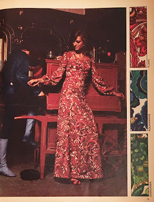 A woman in a long, flowing paisley dress. She is dancing.