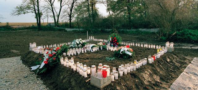 Velas y arreglos florales en una fosa común en Ovcara, Croacia, donde unos 200 civiles fueron asesinados en 1994.UN Photo/Eric Kanalstein