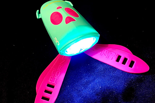 A pink and turquoise bike and scooter light which makes 25 different noises by pressing the pink buttons or the remote trigger