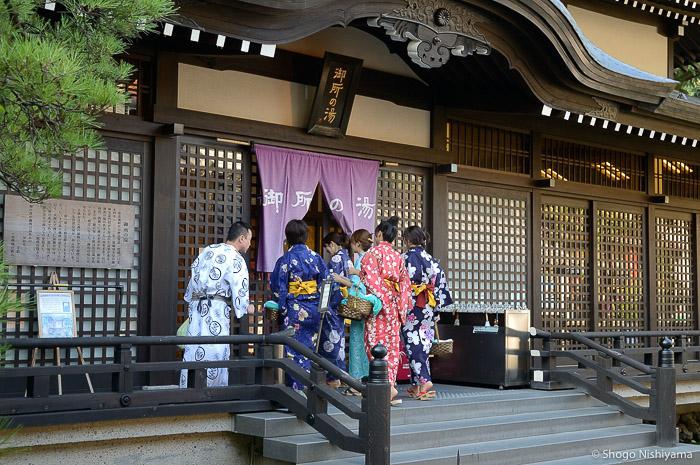 groupe de baigneurs en yukata à l'entrée du goshono-yu