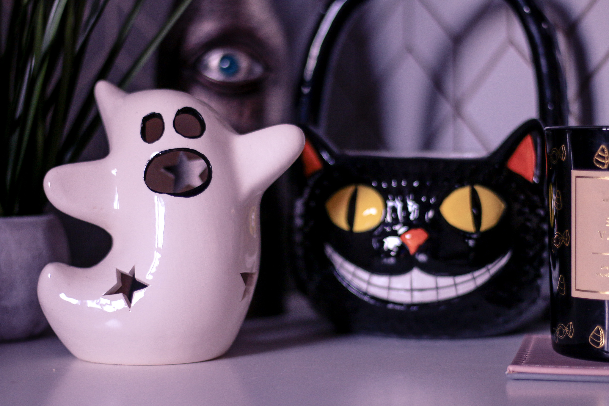 Close up photo of a white Ghost candle holder with a black cat basket in the background