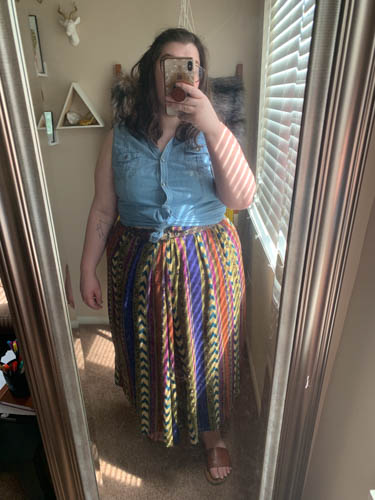 A mirror selfie of an outfit of a chambray sleevless blouse tied in a knot, a patterned maxi skirt, and brown slide sandals.