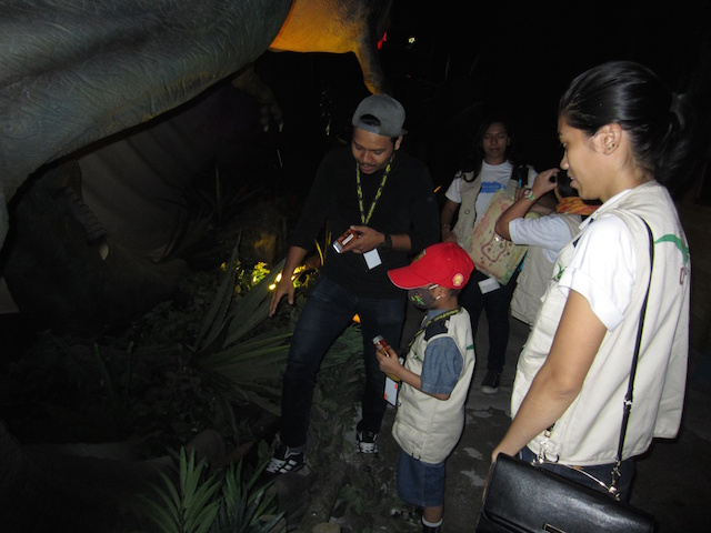 Nik Alik Irfan ( in red cap ) checking out the feet of the Tyrannosaurus Rex at Dinoscovery by Dinosaurs Live!
