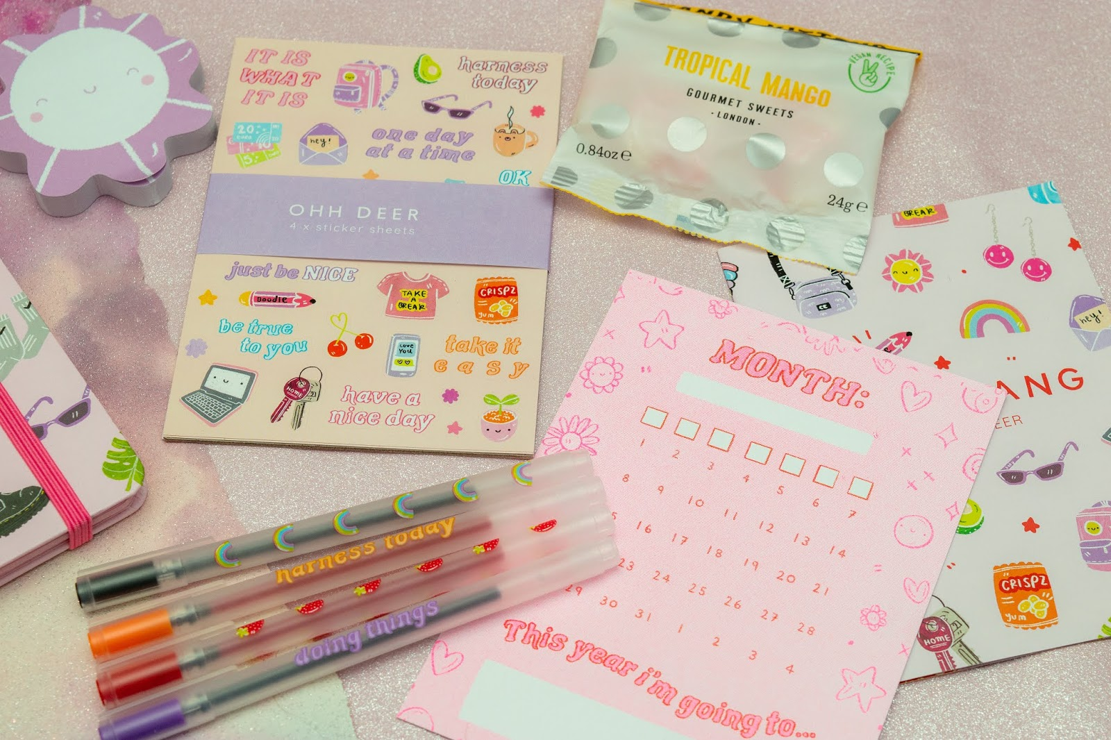 A flat lay of stickers, four pens, a postcard and sweets.