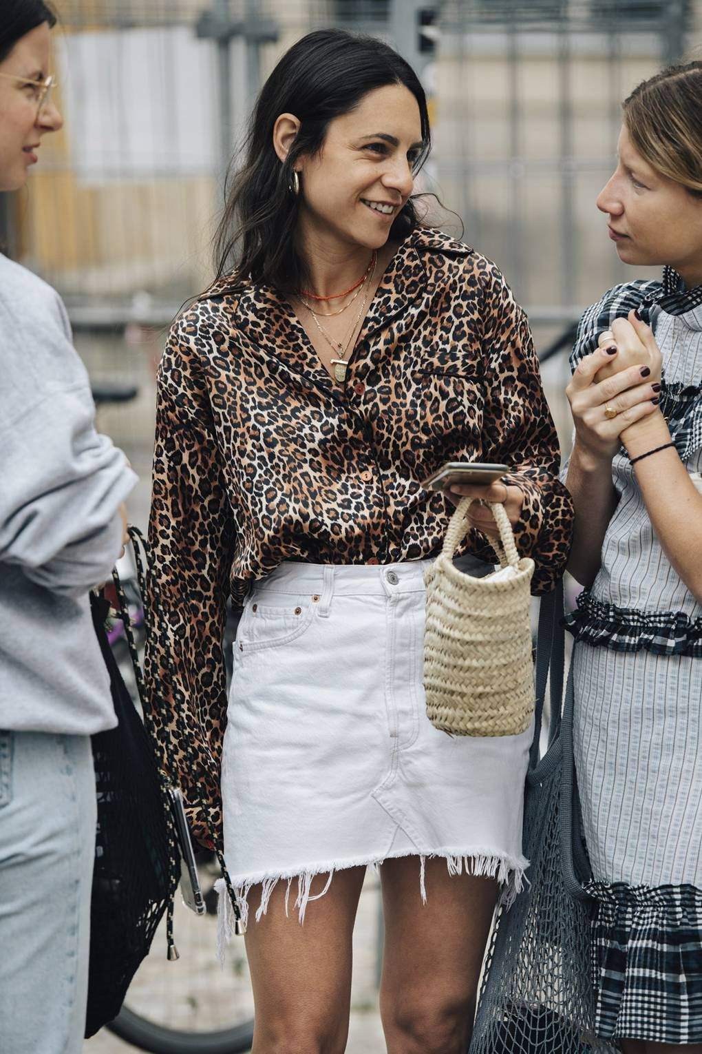 How to wear white denim skirt for summer outfit idea with leopard print shirt, layered necklaces and straw basket tote bag