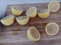 A wooden chopping board with 8 half lemons on it.