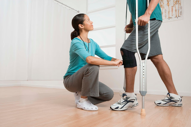 A man on crutches works with his physical therapist