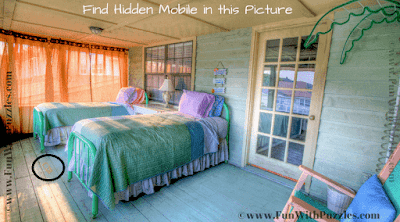 This mobile is lying on the floor between two beds.