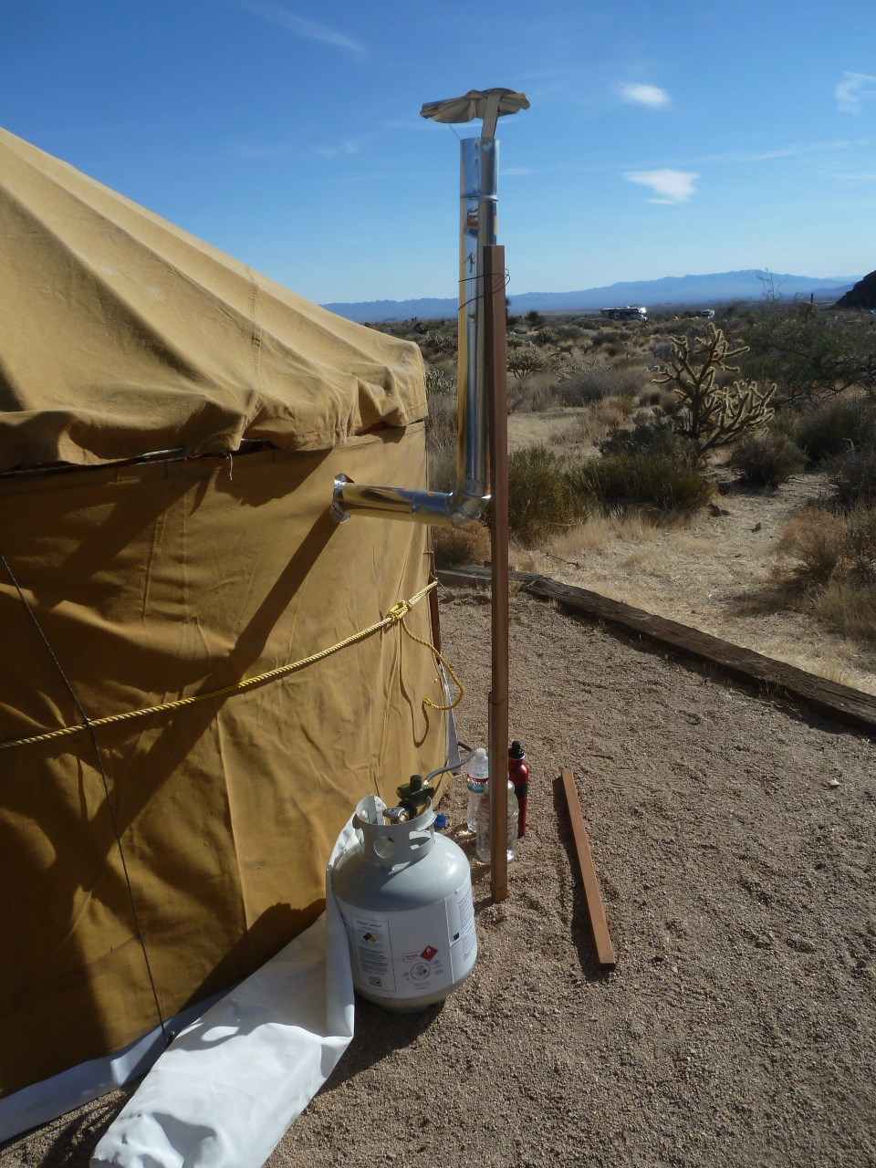 View of the stove pipe outside the tent. The pipe is supported by a length of wood. The propane tank stays outside. & Nomadic Life: A Propane Heater for the Yurt