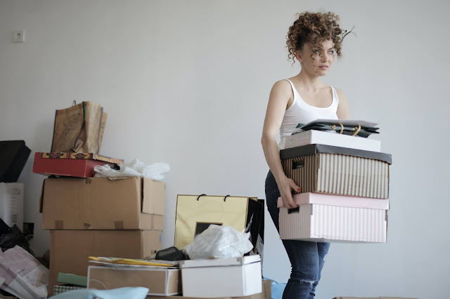 A woman moving lots of boxes and clutter