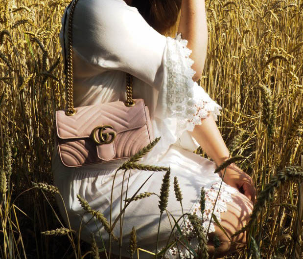 White dress with a Gucci bag and a straw hat