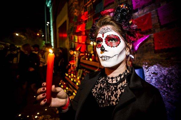 عيد الهالوين موعد الأرواح والشياطين - الصورة تضم امرأة متنكرة بماسك مخيف في ليلة الهالوين وتحمل شمعة في مكان مظلم به ألوان غامقة وحمراء دمائية مخيفة