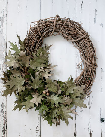 Dress up your front door this fall with a pretty grapevine wreath covered in preserved green oak leaves.
