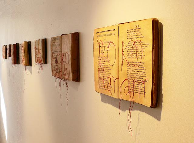 Livres brodés au mur. Vue de l'exposition Espace Rabot