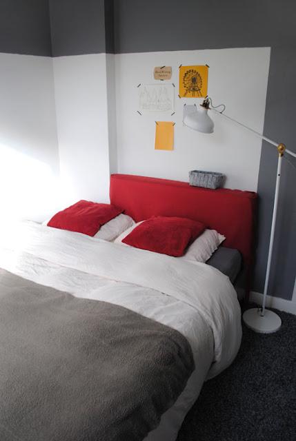 Grafische slaapkamer met wit en grijs als hoofdkleuren en donkerrood en okergeel als accent.