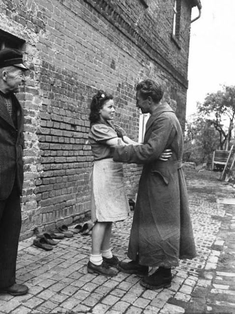 After being released from Allied detention, German POW Heinz Pelschner reunited with his wife, June 1945. Check out the wood shoes along the wall