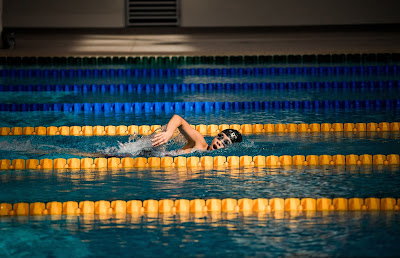 Picture of a child doing laps in the lane of a pool. Swim Teacher or Coach What is The Difference?