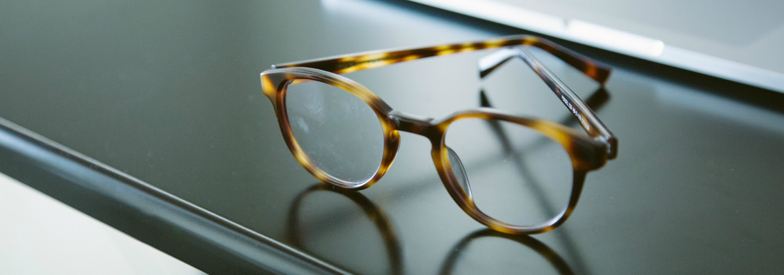 animal print frame glasses on a black desk