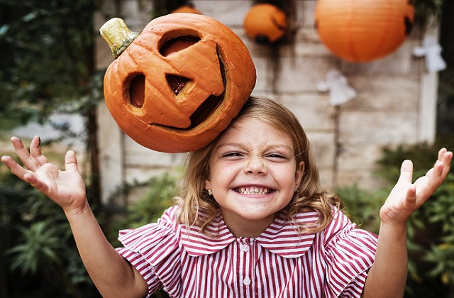 little girl with jack-o-lantern headpiece happy