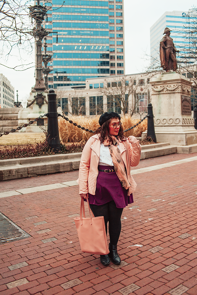 An outfit of a black beret, pink peplum faux leather jacket, vintage white pleated blouse, pink geometric skull print scarf tied in a bow, purple skater skirt, black tights and black boots.