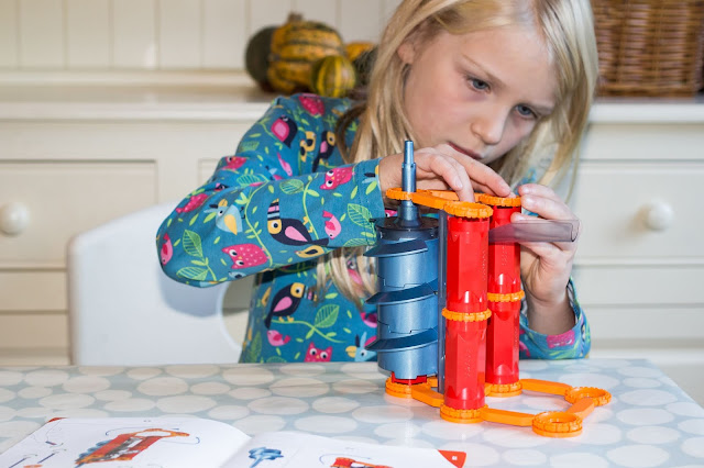Concentration on the face of a child assembling plastic pieces