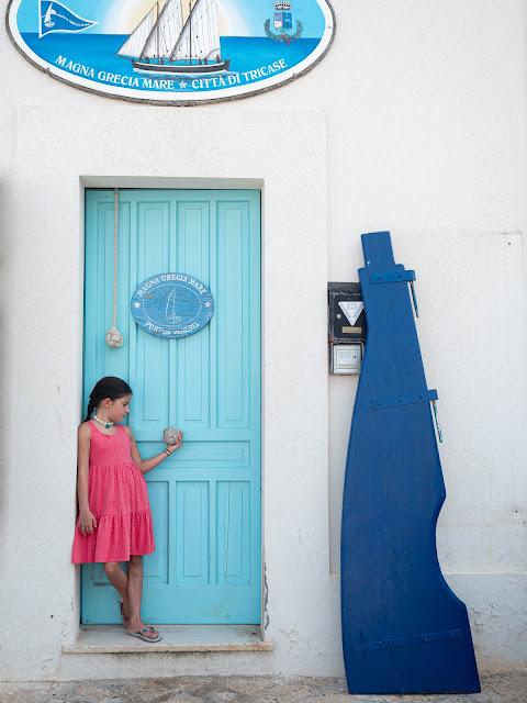 Niña con vestido rosa apoyada sobre puerta azul turquesa y fachada blanca