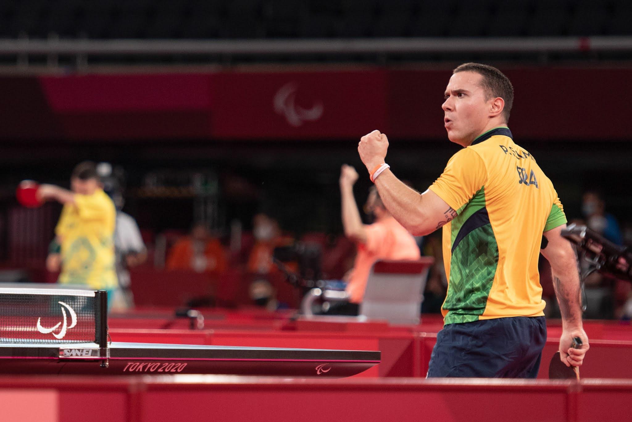 Paulo Salmin, quase que de costas para foto, vibra de punhos cerrados; ele está de camiseta amarela