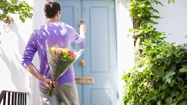 A guy with flowers in his hands hidden behind him and knocking at a door