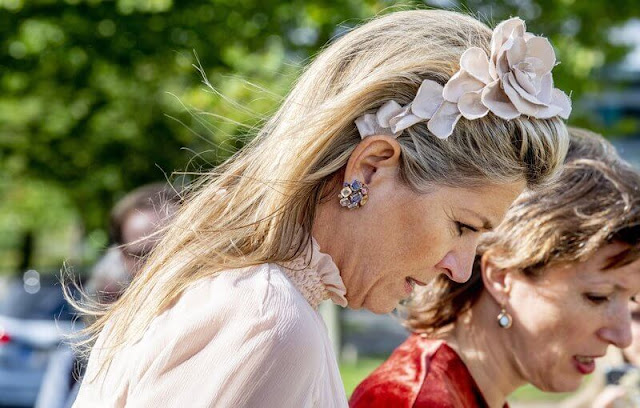 Queen Maxima wore a light baby pink tulle top and pink wide leg trousers. Salvatore Ferragamo flower heel pump shoe
