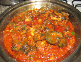 Snail tomato stew in a cooking pot