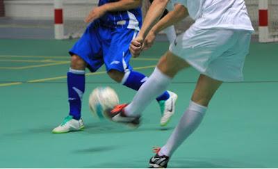 Närbild på spelares ben och boll vid inomhusfotboll.