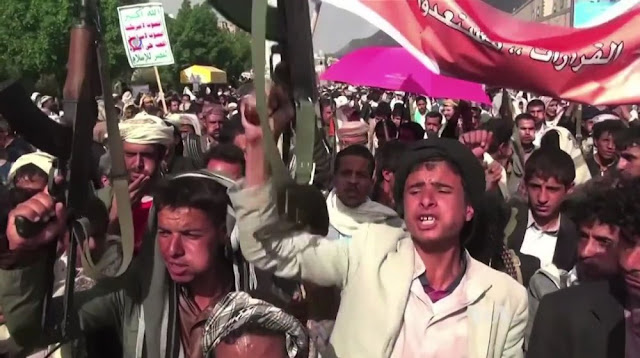 Image Attribute: A file photo of Houthi forces protesting against Arab-led Coalition airstrikes / Source: Wikimedia Commons