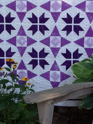 Close up of purple and white star quilt