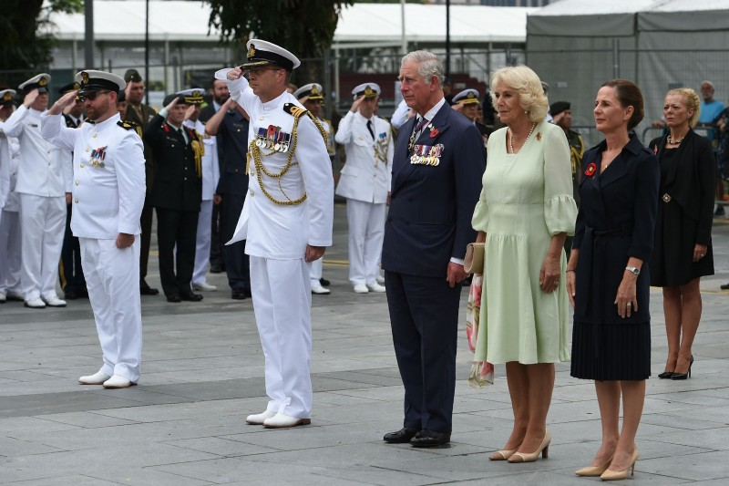 Britain's Prince Charles, Prince of Wales and Camilla, Duchess of Cornwall observe a minute of silence during a wreath laying ceremony at The Cenotaph war memorial in Singapore on October 31, 2017.