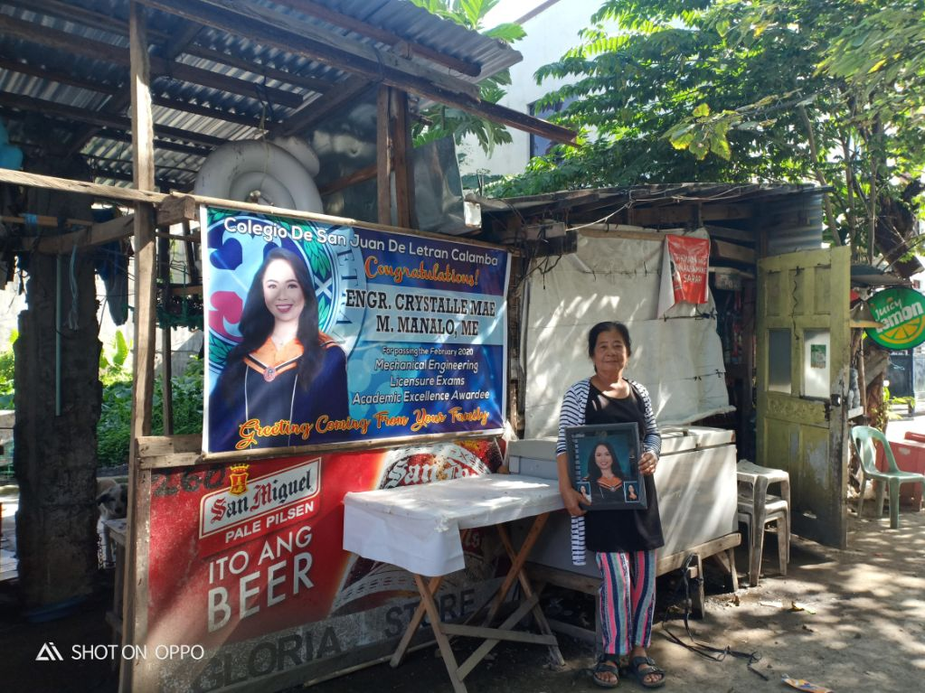 Nanay Gloria happily posed for a photo with the tarpaulin
