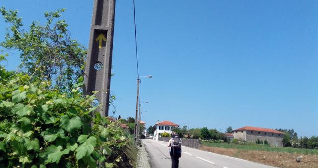 peregrina de Santiago de Compostela na estrada e uma seta amarela no poste